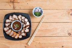 Deep Fried Crispy Pork Belly Cooked with Garlic and spicy dipping sauce. On wooden table background stock photos