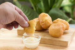 Deep fried dough bun dip in sweetened condensed milk Stock Photo