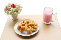 Deep-fried dough stick with pink cold drink and flower in jar on. Wood table/isolated on white background/angle view Royalty Free Stock Photos