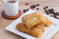 Deep-fried doughstick and coffee on wood background stock images