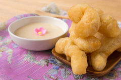 Deep-fried doughstick and condensed milk for dipping on wood tab Royalty Free Stock Photo