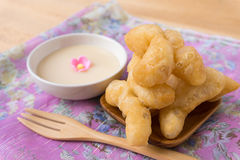 Deep-fried doughstick and condensed milk for dipping on wood tab Royalty Free Stock Images