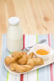 Deep-fried doughstick with orange jam and a bottle of milk. On the table Royalty Free Stock Photography