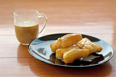 Deep fried doughstick with sweetened condensed milk and coffee Royalty Free Stock Photo