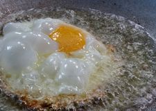 Deep Fried egg in hot foaming oil in the pan in the kitchen Stock Image