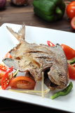 Deep fried fish. A deep fried fish with tomato and onion Stock Image