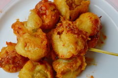Deep fried fish ball dressing chili sauce and wooden stick Royalty Free Stock Image