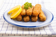 Deep fried fish finger made from alaska pollock fish. With slice lemon and parsley on a plate royalty free stock image