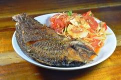 Deep fried mango fish dressing papaya spicy salad topping salty egg. On plate royalty free stock image