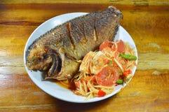 Deep fried mango fish and papaya spicy salad topping salty egg on dish. Deep fried mango fish and papaya spicy salad topping salty egg on white dish Royalty Free Stock Photo
