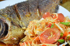 Deep fried mango fish and papaya spicy salad topping salty egg on dish Stock Photo