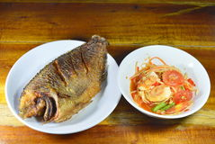 Deep fried mango fish and papaya spicy salad topping salty egg. On table royalty free stock image