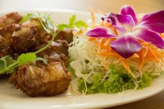 Deep-fried pork belly, that marinate with fish sauce and spices. On white ceramic plate, Thai recipe Stock Photography