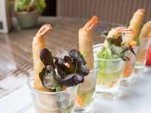 Deep fried shrimp spring rolls. In glass on white plate at restaurant Stock Image