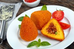 Deep fried sicilian arancini, close up. Fried arancini - classic italian cuisine, risotto cones stuffed with meat ragu, and green peas on white plate, tomato Royalty Free Stock Photography