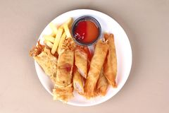 Deep fried spring roll,and frence fries sreved with tomato souce. Food for health,Deep fried spring roll as Por Peai J ,and frence fries sreved with tomato souce stock photos