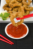 Oriental Deep Fried Squid Rings. Deep fried squid rings coated in panko breadcrumbs served with chili sauce and lemon wedges stock photos
