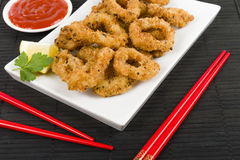 Oriental Deep Fried Squid Rings. Deep fried squid rings coated in panko breadcrumbs served with chili sauce and lemon wedges Stock Photo