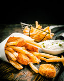 Deep fried takeaway fish and chips. Deep fried takeaway crumbed fish portions and golden potato chips served in a disposable paper cone with tartar sauce on an royalty free stock photo