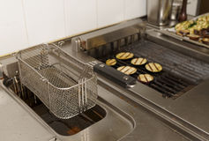Deep fryer and grill on commercial kitchen Stock Image