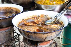 Deep frying Fish on the street in Bangkok. Deep frying fish in oil on the streets of Bangkok Thailand. Cooking utensils in the big pot stock photography