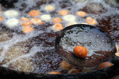 Deep frying medu vada in the  pan. Medu Vada is a savoury snack from South India, very common street food in the India. Royalty Free Stock Photos
