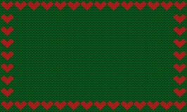 Deep green fabric knitted background framed with knit red hearts Stock Photos