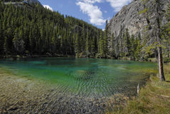 Deep Green Lake in the Rockies. Emerald green alpine Grassi Lake near Banfff and Canmore British Columbia Royalty Free Stock Photography