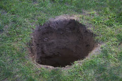 Deep hole in ground or lawn Royalty Free Stock Photo
