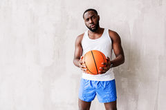 Deep looking bearded athlete standing by wall with basket-ball in arms Stock Photos