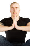 Deep meditation. Isolated man with tatoo on his right arm in black shirt in deep meditation on white background Royalty Free Stock Photos