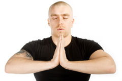 Deep meditation. Isolated man with tatoo on his right arm in black shirt in deep meditation on white background Stock Photography