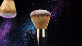 Deep ocean powder color splash and silver brush for makeup artist or beauty blogger in black background