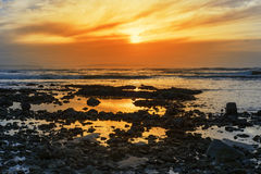 Deep orange reflections at rocky beal beach Stock Images
