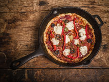 Deep pan pizza on wooden table. A delicious deep pan pizza on a wooden table stock photo