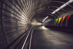 Deep perspective into dark, winding underground tunnel stock image