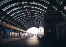 Deep perspective of rails and a train at Milan central station. Colored windows in ceiling, bright light shining in in the distance. Milano, Italy Royalty Free Stock Images