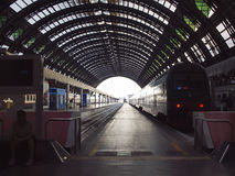 Deep perspective of rails and train at Milan central station. Royalty Free Stock Images