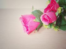 Deep pink artificial roses, vintage style background. On wooden table royalty free stock photos