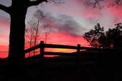 Shades of color at sunset over a rural fence. Deep pink, orange sunset over a ranch in rural Missouri. Part of the Ozark chain of mountains in Ironton, Missouri stock image