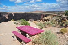 Deep Pink picnic table at the edge of 500 foot cliff. Deep pink purple picnic table at the edge of a 500 foot fall off cliff near Cameron Arizona royalty free stock photography