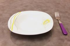 Deep plate with fork. Deep plate with purple fork on table royalty free stock image