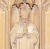 Deep in Prayer. A carving of a man praying. This historic carving is located in Winchester Cathedral in Hampshire, England and was carved over 500 years ago. I royalty free stock images