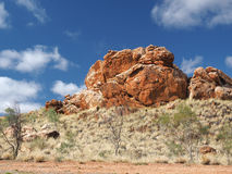 Deep red outback rock formation under blue sky. Near Alice Springs, Australia, June 2015 Stock Photos