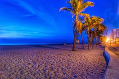 Early sunrise long exposeure of the beach in part of the boardwalk in Hollywood Beach, Florida. Deep rich blue sky as the sun comes up over the ocean Royalty Free Stock Photos