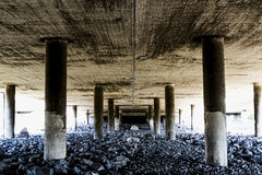 Deep and rough perspective from under a concrete bridge. A rocky and grimy part of an urban landscape Royalty Free Stock Image