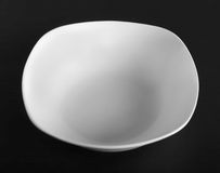Deep round porcelain dish. White bowl on black background, front view Royalty Free Stock Images