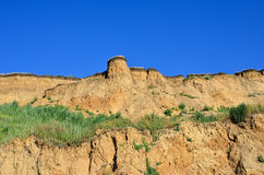 Deep sandy cliff on the background of blue sky. Royalty Free Stock Images