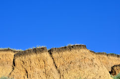 Deep sandy cliff on the background of blue sky. Stock Image