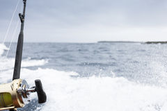 Deep-sea fishing with boat spray. Fishing rod planted in the boat with sea spray Royalty Free Stock Photo